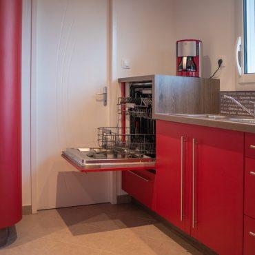 lave vaisselle sureleve d une cuisine rouge 370x370 - Cuisine rouge courbée et plan de travail décors bois arrondi